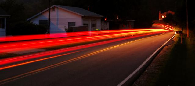 silnice, na které jsou vidět červené čáry jako za rychlým automobilem, kolem jsou domy