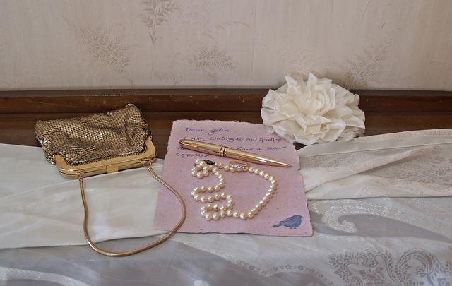 Kovová kabelka-psaníčko, vedle ní položená šňůra perel a dopis